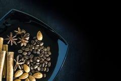 Spezie aromatiche con i chicchi e le mandorle di caffè su un fondo nero Immagini Stock