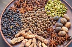 Spezie aromatiche su un piatto scuro - anice stellato, pepe fragrante, radice del calamo aromatico, cannella, alto vicino della n Fotografie Stock