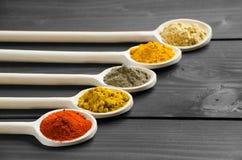 Spezie asciutte della polvere in cucchiai di legno di miscelazione alla tavola Fotografia Stock Libera da Diritti