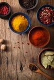 Spezie in ciotole: pepe rosa e nero, polvere della paprica, curry, b Fotografia Stock Libera da Diritti