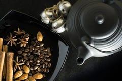 Spezie dei chicchi di caffè con una teiera e delle campane su un fondo nero Fotografia Stock