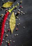 Spezie del peperone e foglia di alloro pungenti sull'albero nero Vista da sopra Fotografie Stock
