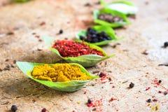 Spezie differenti spruzzate in foglie verdi Immagine Stock