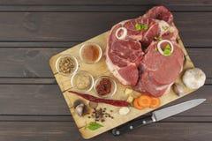 Spezie e stinco crudo del manzo sul tagliere Preparazione dell'alimento piccante Decorazioni per il menu Fotografia Stock