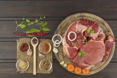 Spezie e stinco crudo del manzo sul tagliere Preparazione dell'alimento piccante Decorazioni per il menu Immagini Stock Libere da Diritti