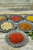 Spezie ed erbe in ciotole del metallo Ingredienti di cucina e dell'alimento Immagine Stock