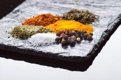 Spezie ed erbe differenti su un'ardesia nera Spezie indiane Ingredienti per cucinare Concetto sano di cibo Varie spezie su dar Immagini Stock