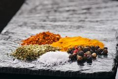 Spezie ed erbe differenti su un'ardesia nera Spezie indiane Ingredienti per cucinare Concetto sano di cibo Varie spezie su dar Fotografia Stock