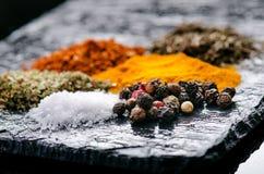 Spezie ed erbe differenti su un'ardesia nera Spezie indiane Ingredienti per cucinare Concetto sano di cibo Varie spezie su dar Fotografie Stock Libere da Diritti