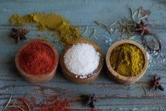 Spezie erbe Curry, sale, zafferano del pepe, curcuma, masala di tandori ed altro su un fondo rustico di legno Immagine Stock