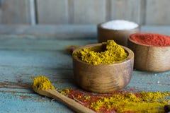 Spezie erbe Curry, sale, zafferano del pepe, curcuma, masala di tandori ed altro su un fondo rustico di legno Immagini Stock