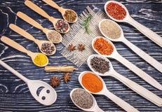 Spezie indiane aromatiche variopinte ed erbe su un marrone di legno della vecchia quercia Immagini Stock
