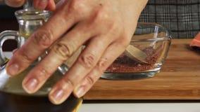 Spezie mescolantesi ed olio ilive di versamento per un guacamole con la ricetta dei vegies video d archivio
