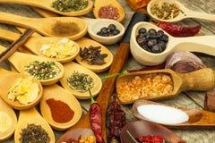 Spezie sui cucchiai di legno Vendite delle spezie esotiche Alimento del condimento Spezie aromatiche Immagini Stock Libere da Diritti
