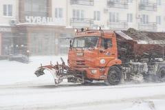 Spezielle Technik entfernt den Schnee von der Straße während eines Schneesturms in der schlechten Sicht Schneesturm in der Stadt  Stockfoto