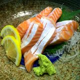 Spezieller deluxer Lachssashimisatz auf Eis trennen mit Wasabi und Gurke, das traditionelle japanische Lebensmittel Maguro-Sashim Lizenzfreies Stockfoto