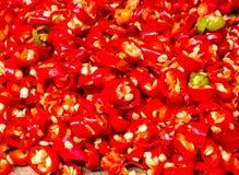 Spezzettamento dei peperoncini rossi a pezzi rossi, primo piano Immagini Stock