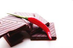 Spezzettamento del cioccolato fondente a pezzi con i peperoncini roventi freschi fotografia stock