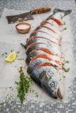 Spezzettamento del salmone a pezzi intero con timo e sale per la griglia Immagine Stock