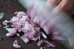 Spezzettamento della cipolla a pezzi con la lama Immagine Stock