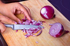 Spezzettamento della cipolla a pezzi rossa in cucina Fotografia Stock