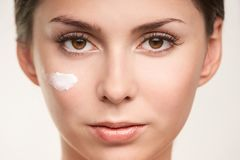 SPF factor cosmetic cream on face. UV care beautiful girl face.  stock image