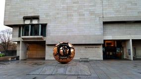 Sphère d'or devant le bâtiment image stock