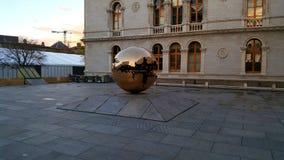 Sphère d'or devant le bâtiment photos stock