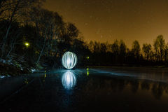 Sphère rougeoyante futuriste sur la surface du lac congelé au fond du paysage de nuit Photographie stock libre de droits