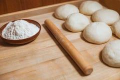 Sphères de la pâte, du roulement-anneau et du plat avec de la farine images libres de droits