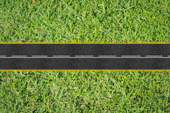 Sphalt road on the green grass royalty free stock photography