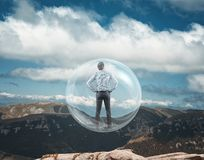 Sphere fly. Businessman standing into an transparent sphere and take off from the top of the montain Stock Photography