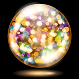 Sphere with sparkles in yellow and orange colors. Orange yellow glass sphere filled with multicolored glowing sparkles with bokeh effect. Sphere with colored Royalty Free Stock Photography
