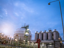 Sphere storage gas tank with silos  at dawn Royalty Free Stock Photos