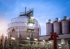 Sphere storage gas tank with silos at dawn Stock Photos
