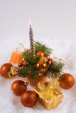 Spheres and silver candles. Christmas orange spheres and silver candles on the white skin Royalty Free Stock Photo