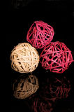 3 Spheres. A still life image of three coloured wicker ball spheres on a black mirrored surface with reflection Royalty Free Stock Image