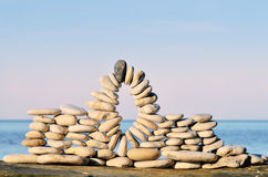 Spherical compound. Arc of pebbles between of the stones on the seashore Royalty Free Stock Photo