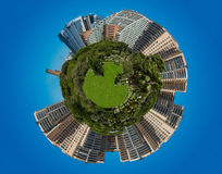 Spherical panorama. Of a green meadow with skyscrapers and chimneys Royalty Free Stock Photo