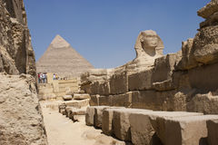 The Sphinx. The Great Sphinx of Giza is a statue of a reclining lion with a human head that stands on the Giza Plateau on the west bank of the Nile, near modern Stock Photos