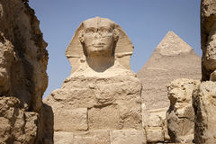 The Sphinx. The Great Sphinx of Giza is a statue of a reclining lion with a human head that stands on the Giza Plateau on the west bank of the Nile, near modern Stock Photography