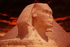 The Sphinx against the Great Pyramids in Giza, Egypt against red dramatic sky. Vacation and travel background. royalty free stock image