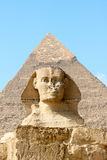 Sphinx on the background of great pyramid Royalty Free Stock Photo