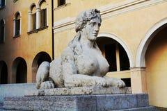 Sphinx and cityscape in Conegliano Veneto, Treviso, Italy. Sphinx statue, cityscape and the Accademy Theatre, in Piazza Cima, in Conegliano Veneto, Treviso Royalty Free Stock Images