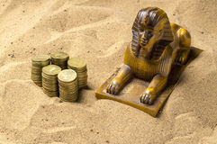 Sphinx and coins in the sand Stock Photography