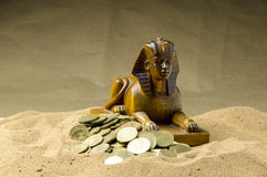 Sphinx and coins in the sand. Sphinx and gold coins in the sand Royalty Free Stock Image