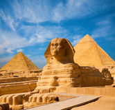 Sphinx Full Body Blue Sky All Pyramids Egypt. Egyptian Great Sphinx full body portrait with head, feet with all pyramids of Menkaure, Khafre, Khufu in background stock photography