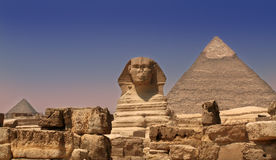 Sphinx Guarding a Pyramid. Sphinx in front of Chephren Pyramid. On the left side is Menkaure Pyramid. Giza, Egypt Royalty Free Stock Images