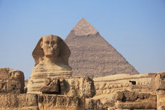 Sphinx and Pyramid. Ancient egyptian Sphinx of Giza with great pyramid of Cheops on the background Royalty Free Stock Photography