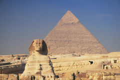 The Sphinx and Pyramid. Ancient egyptian Sphinx of Giza with great pyramid of Cheops on the background Royalty Free Stock Photos